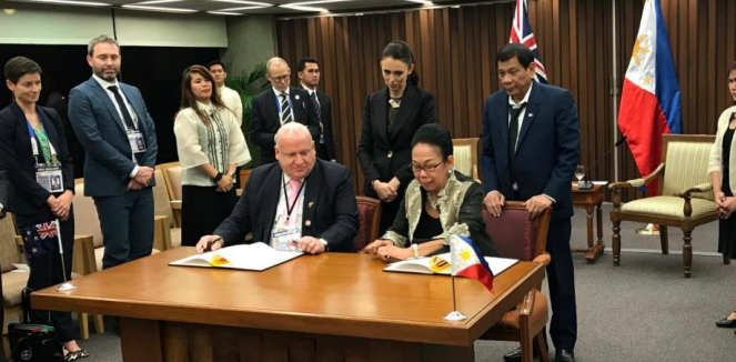 Philippines president Duterte and NZ PM Ardern witness the agreement being signed by David Strachan and Patricia Licuanan. Photo: CHED